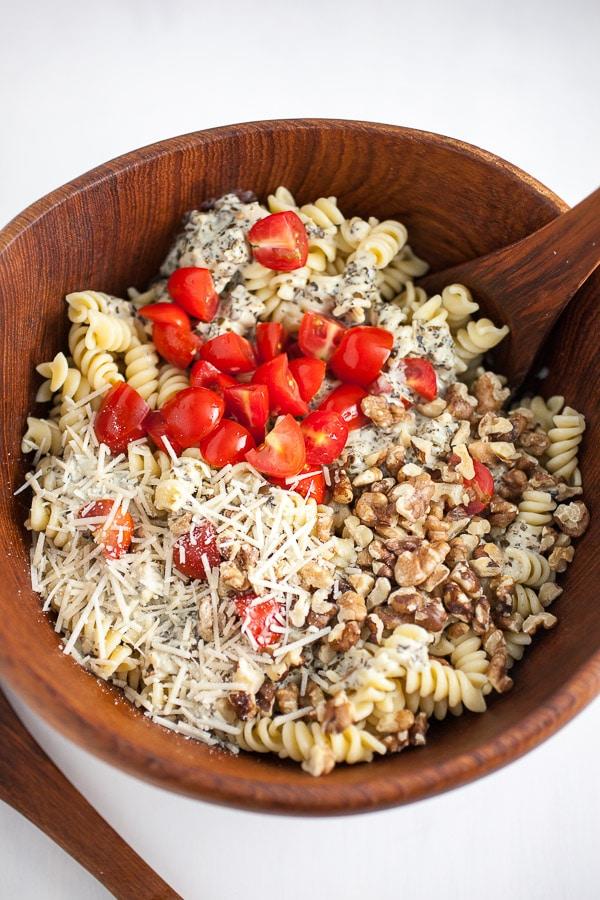 Ingredients for creamy pesto summer pasta salad in bowl