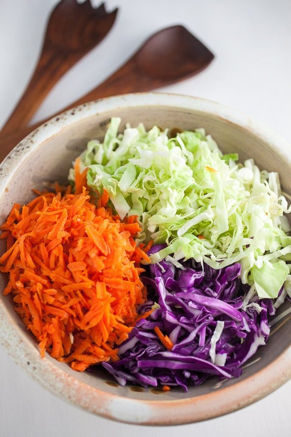Chopped carrots, red cabbage, and green cabbage in bowl