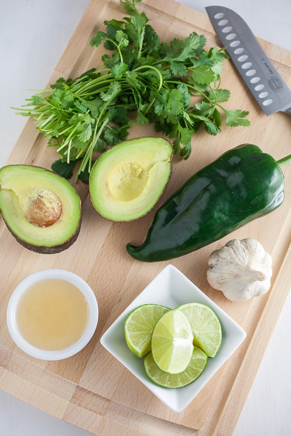 Poblano pepper, avocado, cilantro, garlic, lime, and honey on cutting board